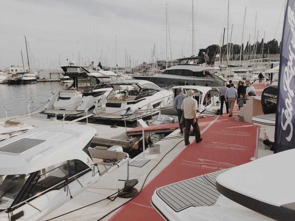 People walking among the yachts