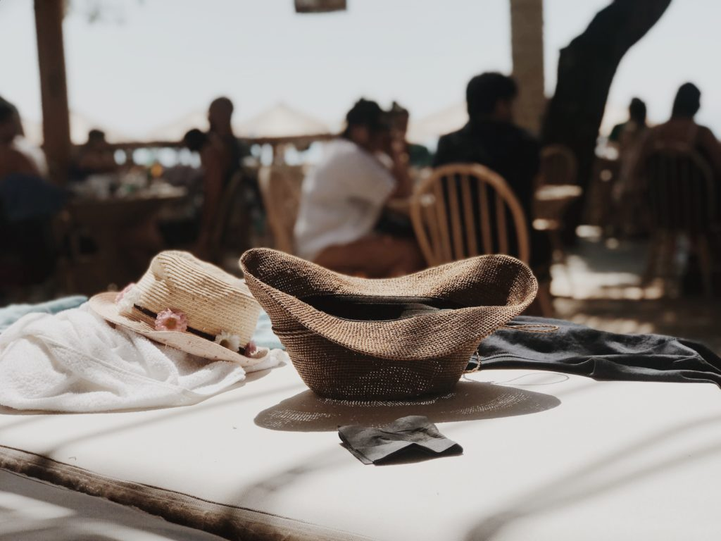 Fashion Women Summer Straw Beach Hat in a cafe on the beach