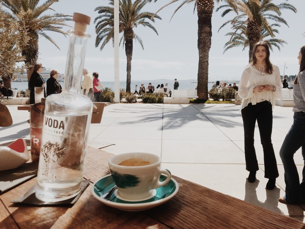 A bottle of water and a cup of coffee with palms in the backgroundn background