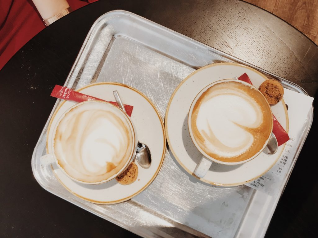 Two cups of coffee on white wooden table. Top view