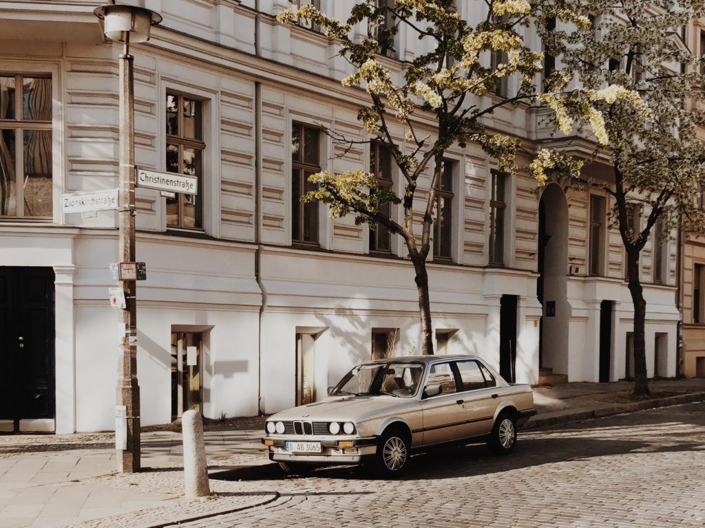BMW at springtime in Berlin, Germany. blossoming tree on the foreground, focus on blossom tree flowers