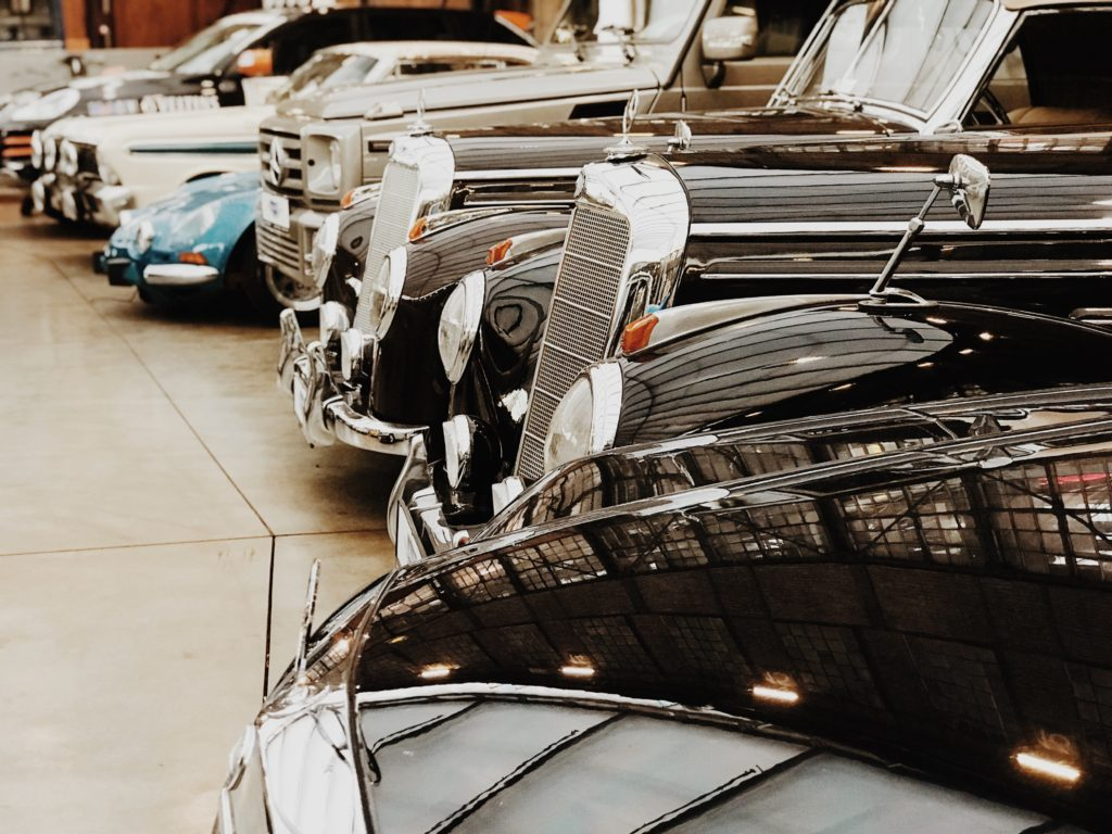 A row of Mercedes Benz vintage cars lined up in a car showroom