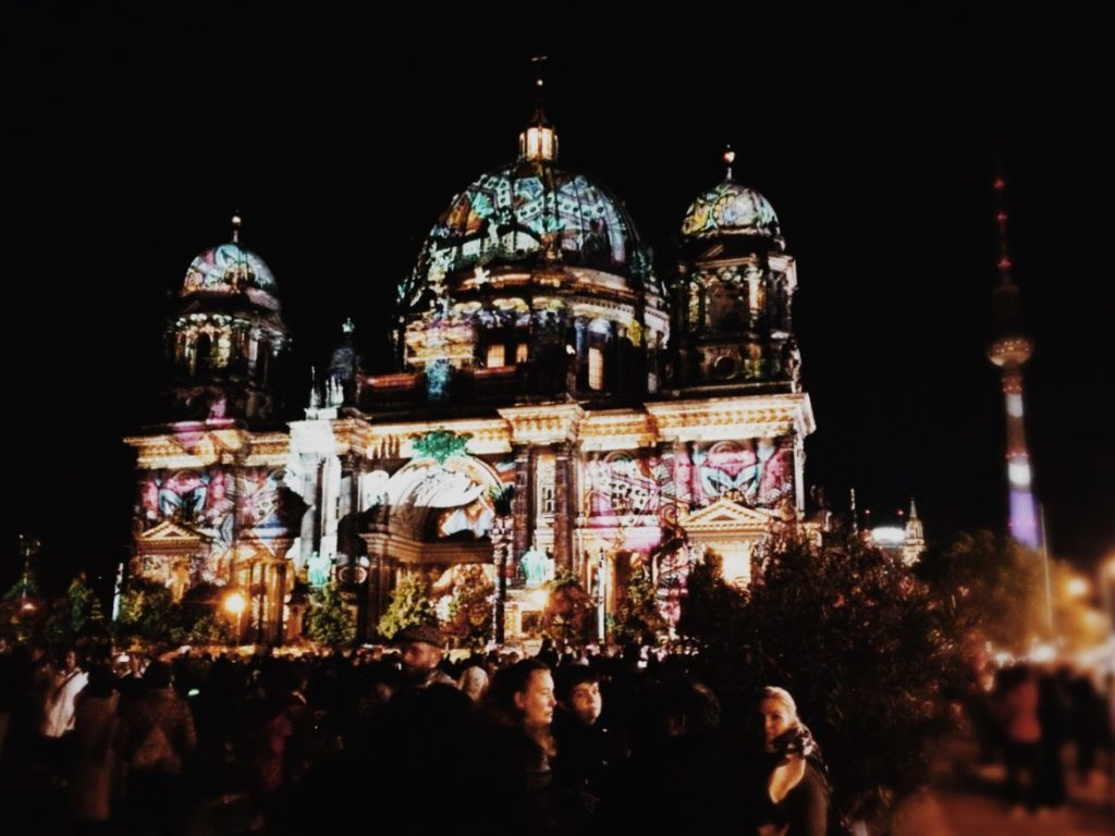 People taking photographs of the Berlin Cathedral covered in lights