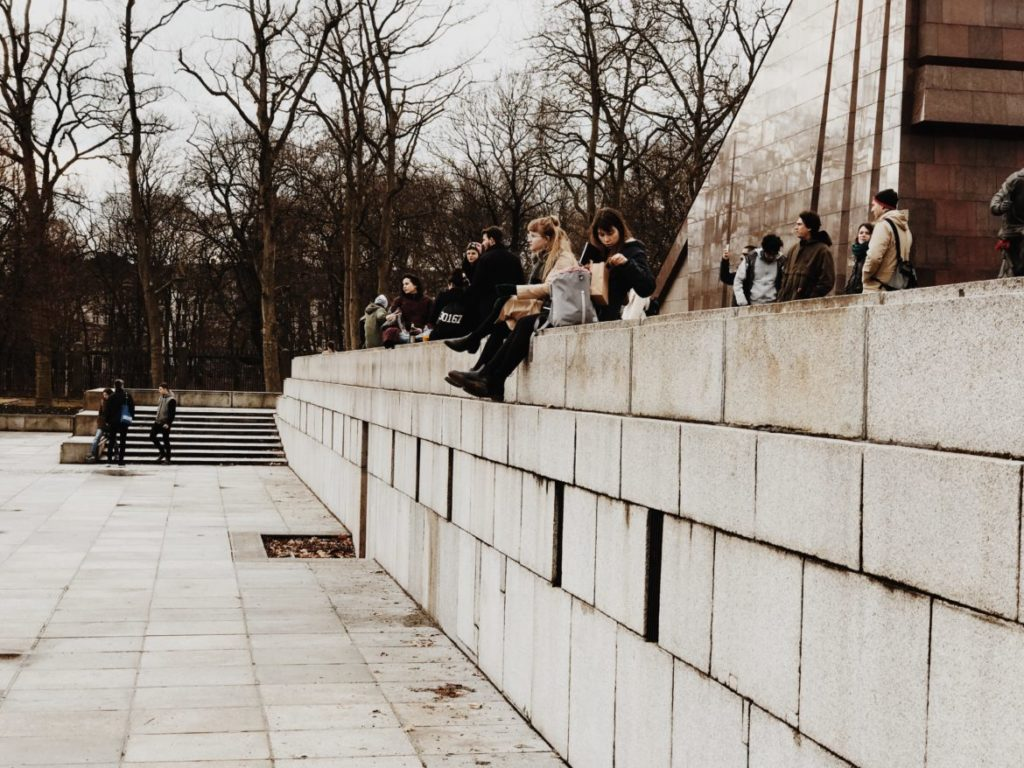 People sitting on stone wall during winter