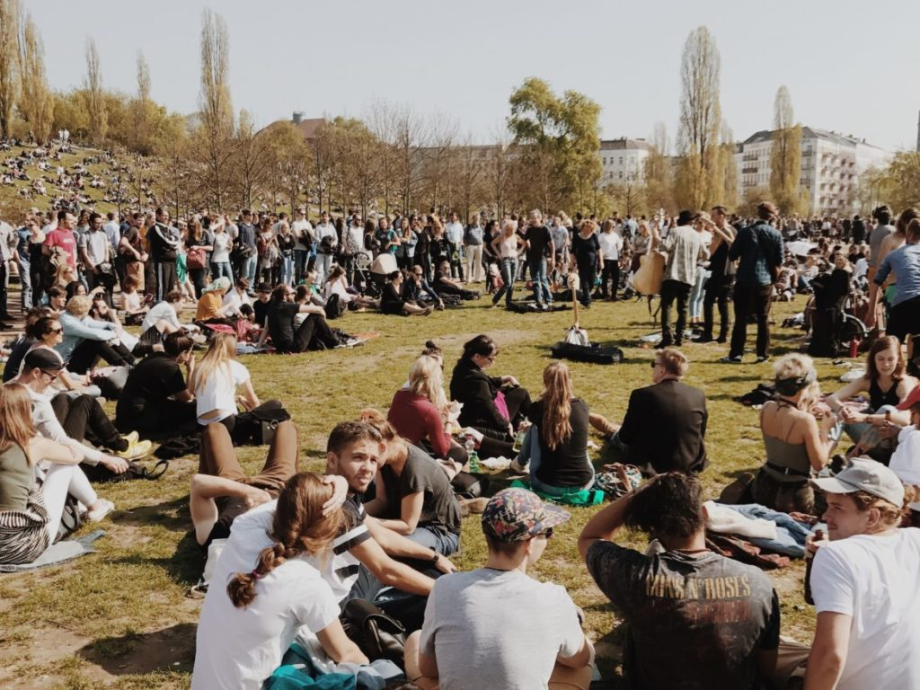 Musician singing and playing guitar in crowded Mauerpark on a sunny summer day