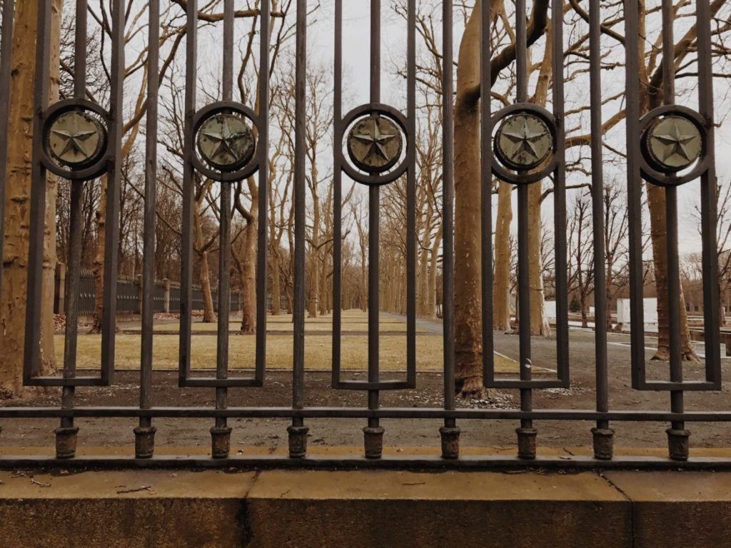 A wrought iron fence by a park