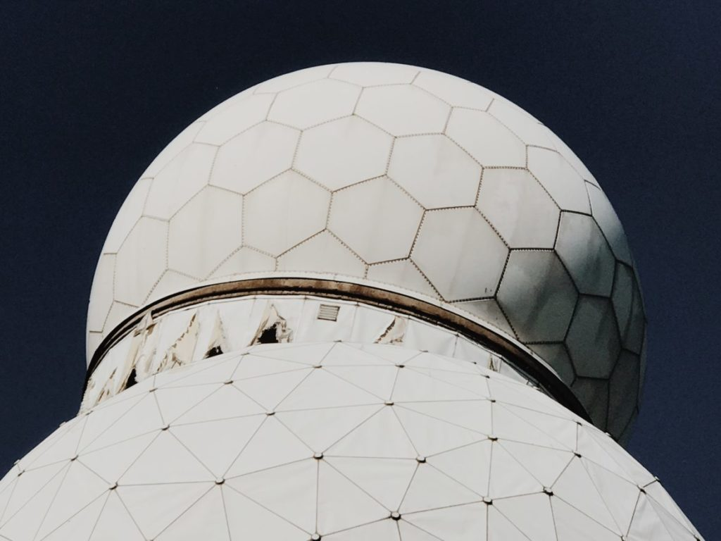 An empty building and geodesic dome at the listening station are covered with various murals