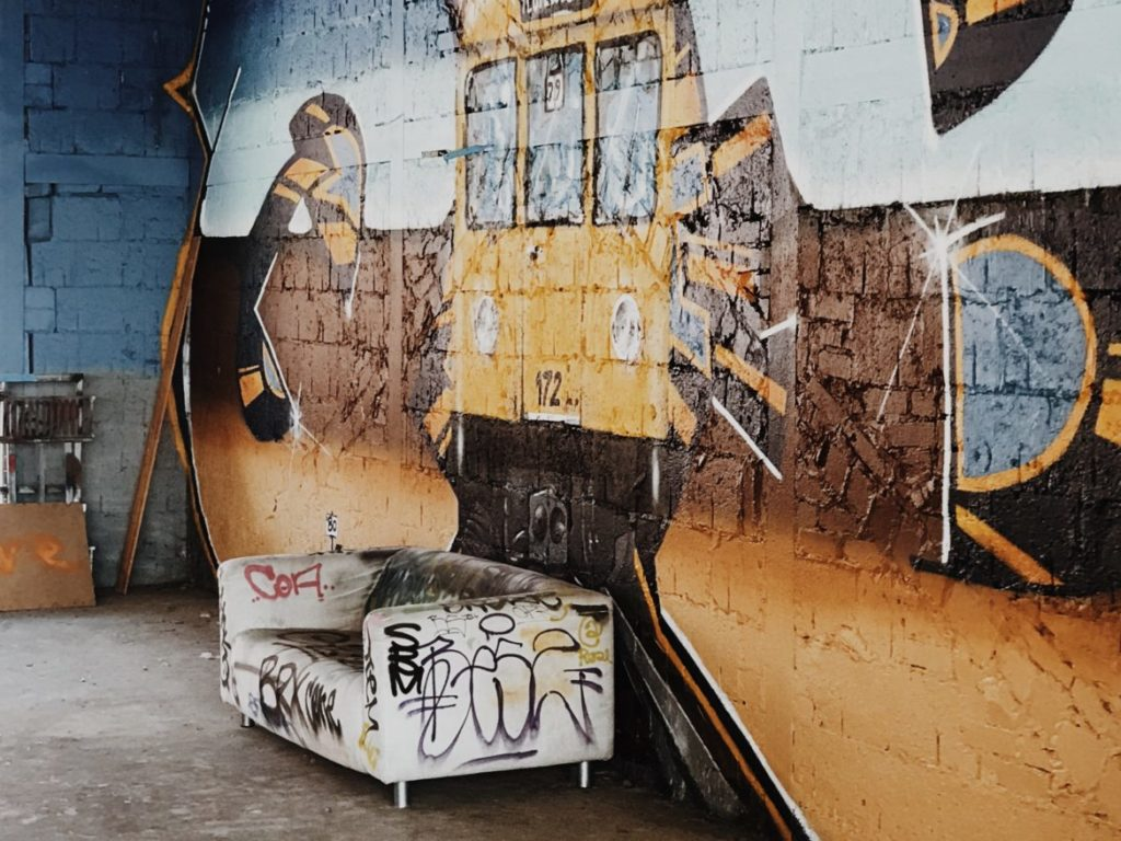 Sofa covered with graffiti with street art background
