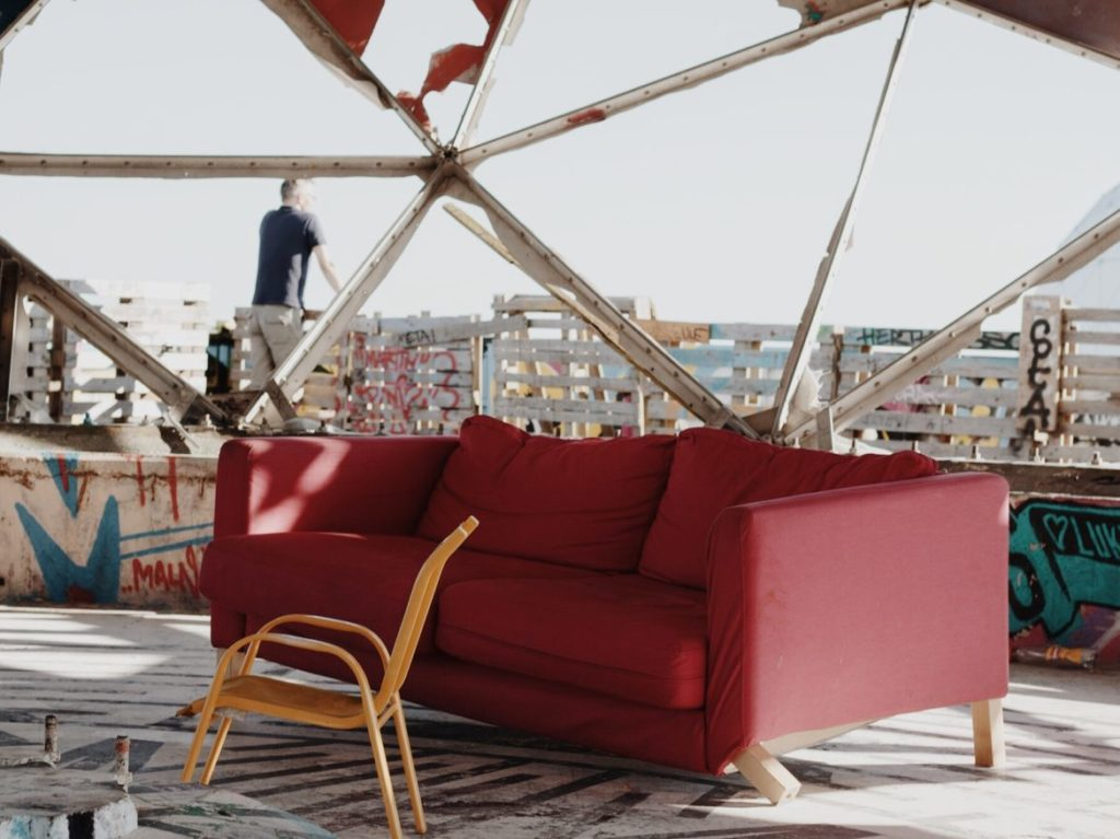 A broken red sofa with yellow chair