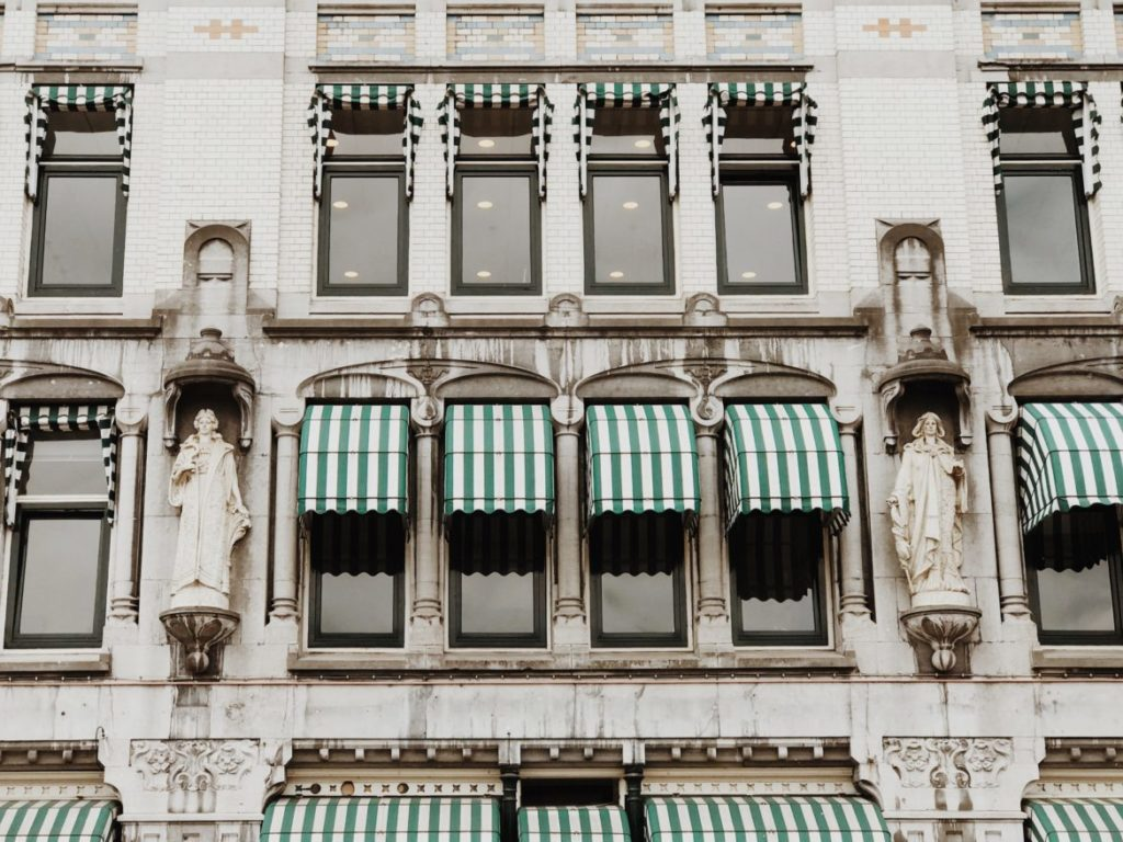 Facade contains a white glazed brick with many decorations and statues of Art-Nouveau style