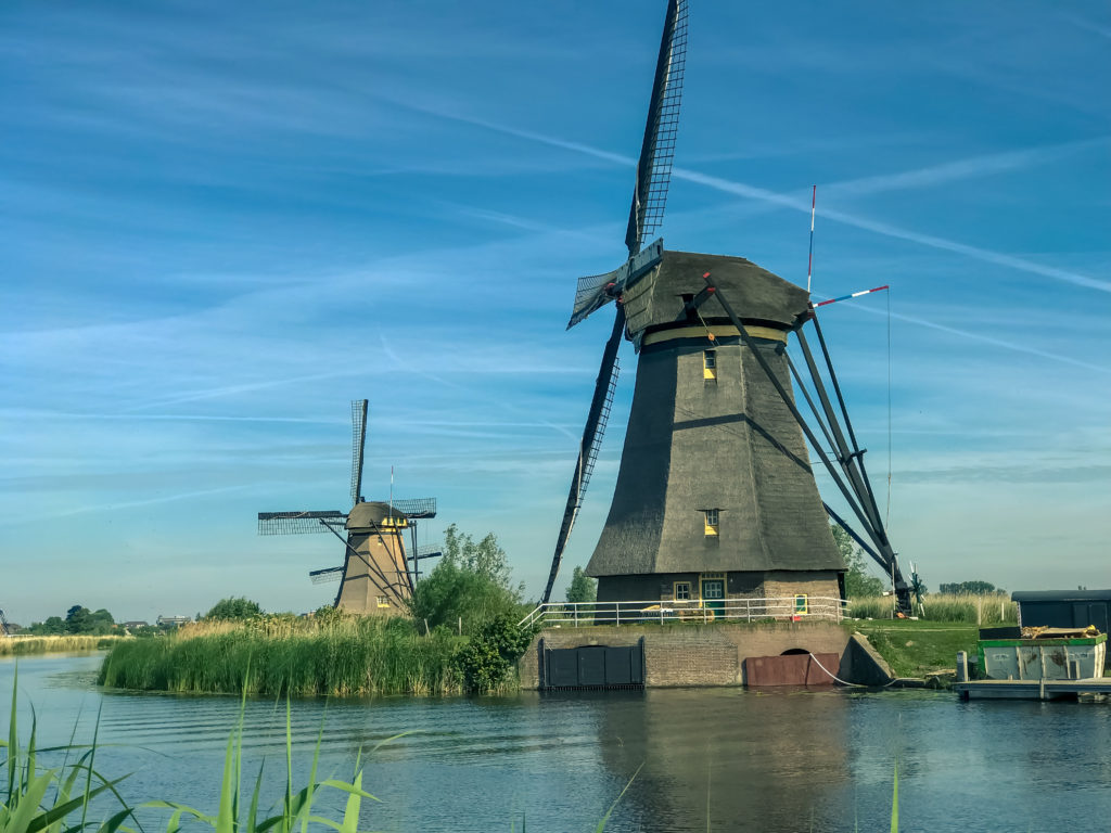 Row of iconic windmills by the water at Kinderdijk, Holland